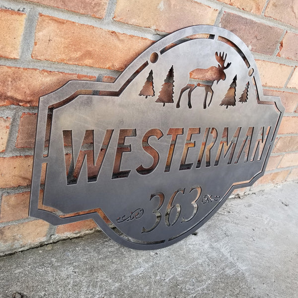 "This is a personalized metal address sign that hangs from a hanging bracket mounted to a wooden post.  The sign features a forest scene with a moose in the center. The sign reads, ""Westerman 363""."