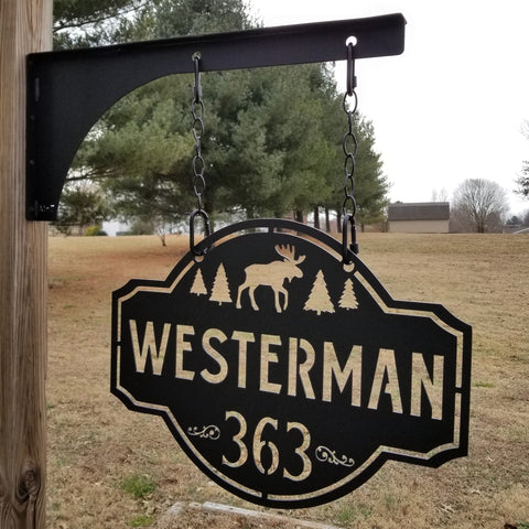 "This is a personalized metal address sign that hangs from a hanging bracket mounted to a wooden post.  The sign is powder coated black and features a forest scene with a moose in the center. The sign reads, ""Westerman 363""."