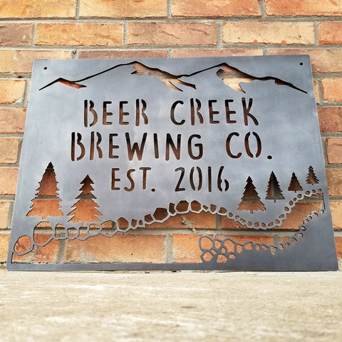 "This sign showcases a mountain background with trees and a creek. The sign reads, "" Beer Creek Brewing Co. Est. 2016""."