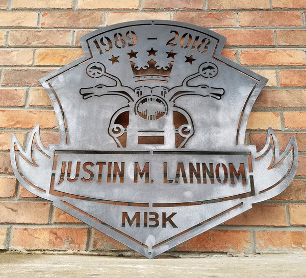 "This is a memorial sign with an established year, dipicting an image of a motorcylce.  The bottom has a name and reads, ""Justin M. Lannom""."