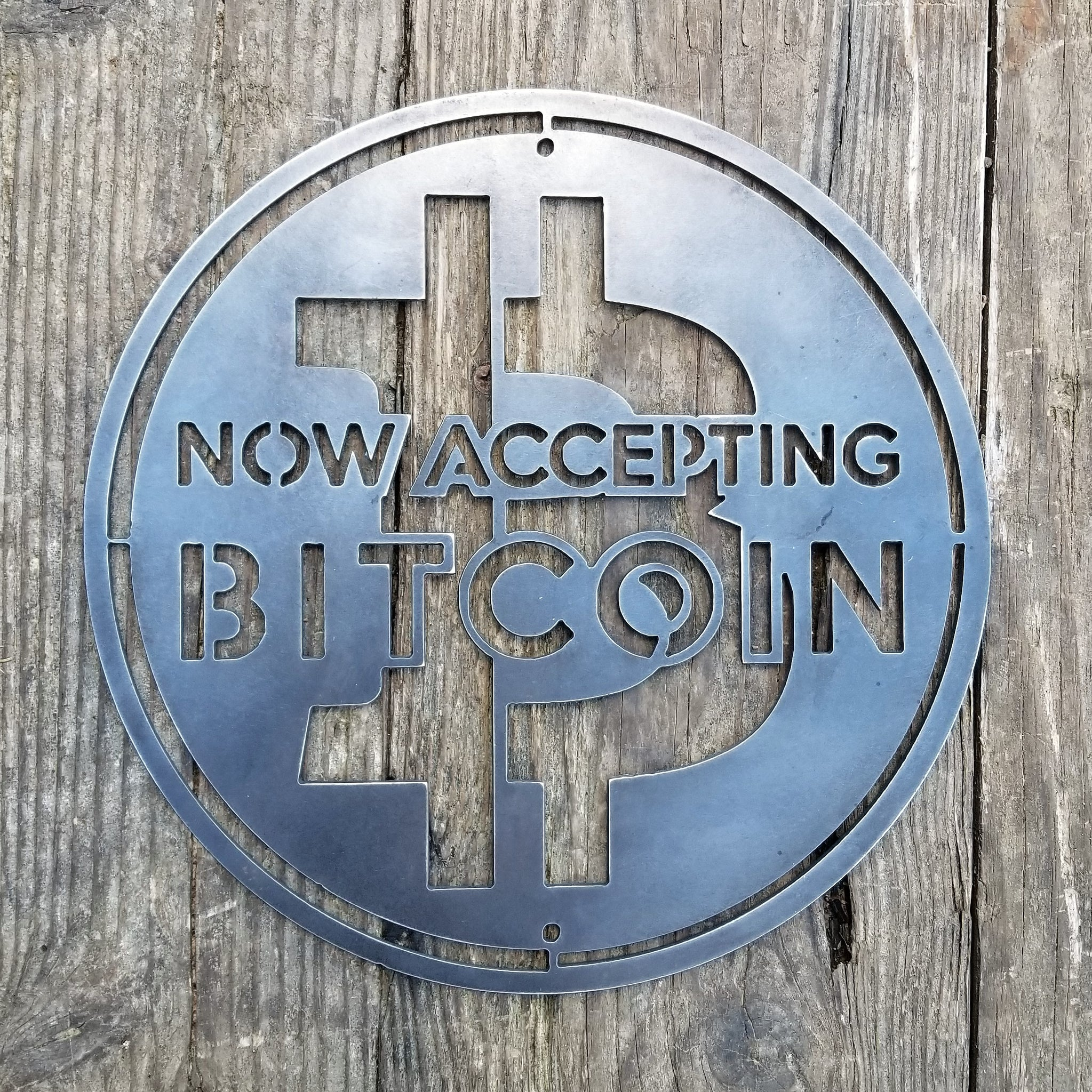 "This is a round sign that reads, ""Now Accepting Bitcoin""."
