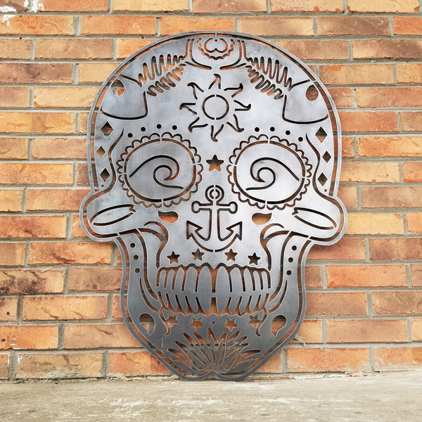 This sign is in the shape of a sugar skull. It is water themed with waves, fish bones, anchors and more.