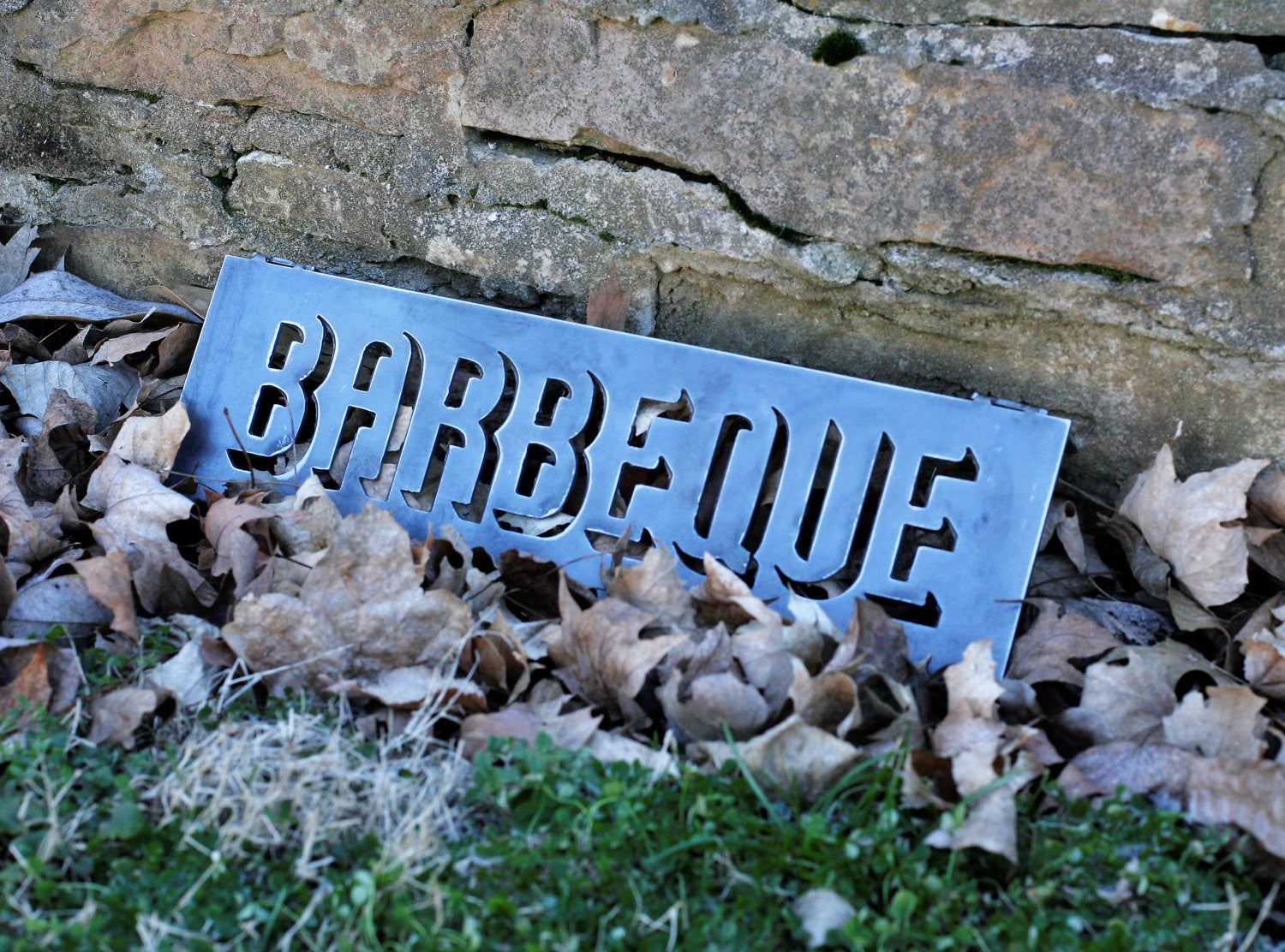 "18"" Metal Sign in a pile of leaves, laying against brick. The sign reads, "" BARBEQUE"""