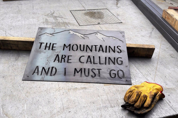 "Custom metal  sign that is in the shape of a rectangle with the image of a mountain range at the top. The sign reads, ""The Mountains are Calling and I Must Go"""