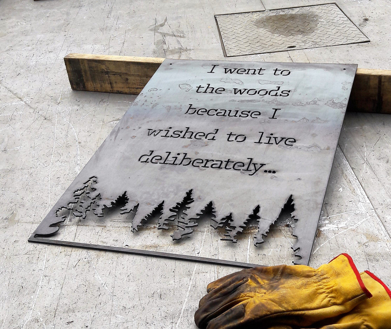 "Rectangle metal sign, with a famous quote said by David Thoreau which reads, ""I Went to the Woods because I Wished to Live Deliberately..."""