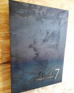 "This is a personalized metal sign that has brackets welded to the back of the sign so that it stands one inch off the wall. It is a modern address sign in the shape of a rectangle and reads, ""447"""
