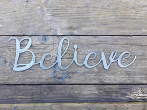 "Metal home decor in the shape of a cursive word. The sign reads, ""Believe""."