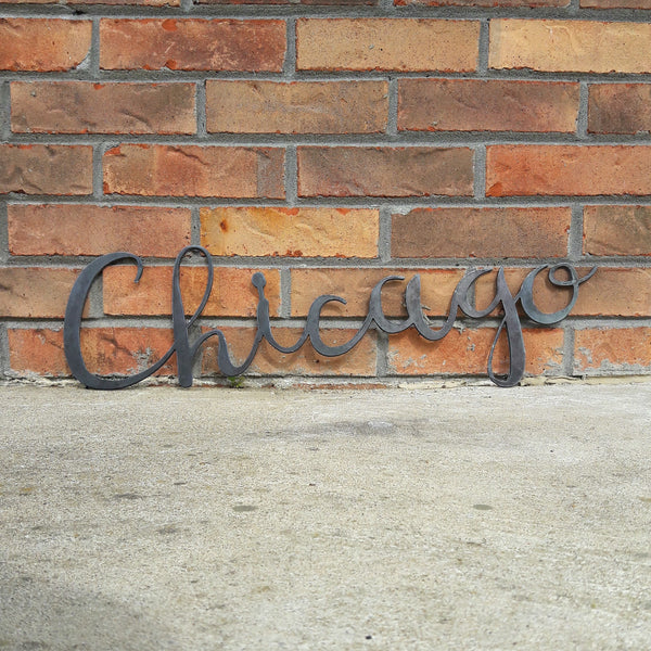 "This metal home decor is in the shape of a cursive word and reads, ""Chicago""."