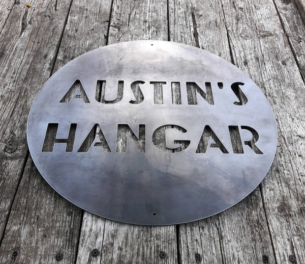 "Round Personalized metal sign that reads, ""Austin's Hangar"""