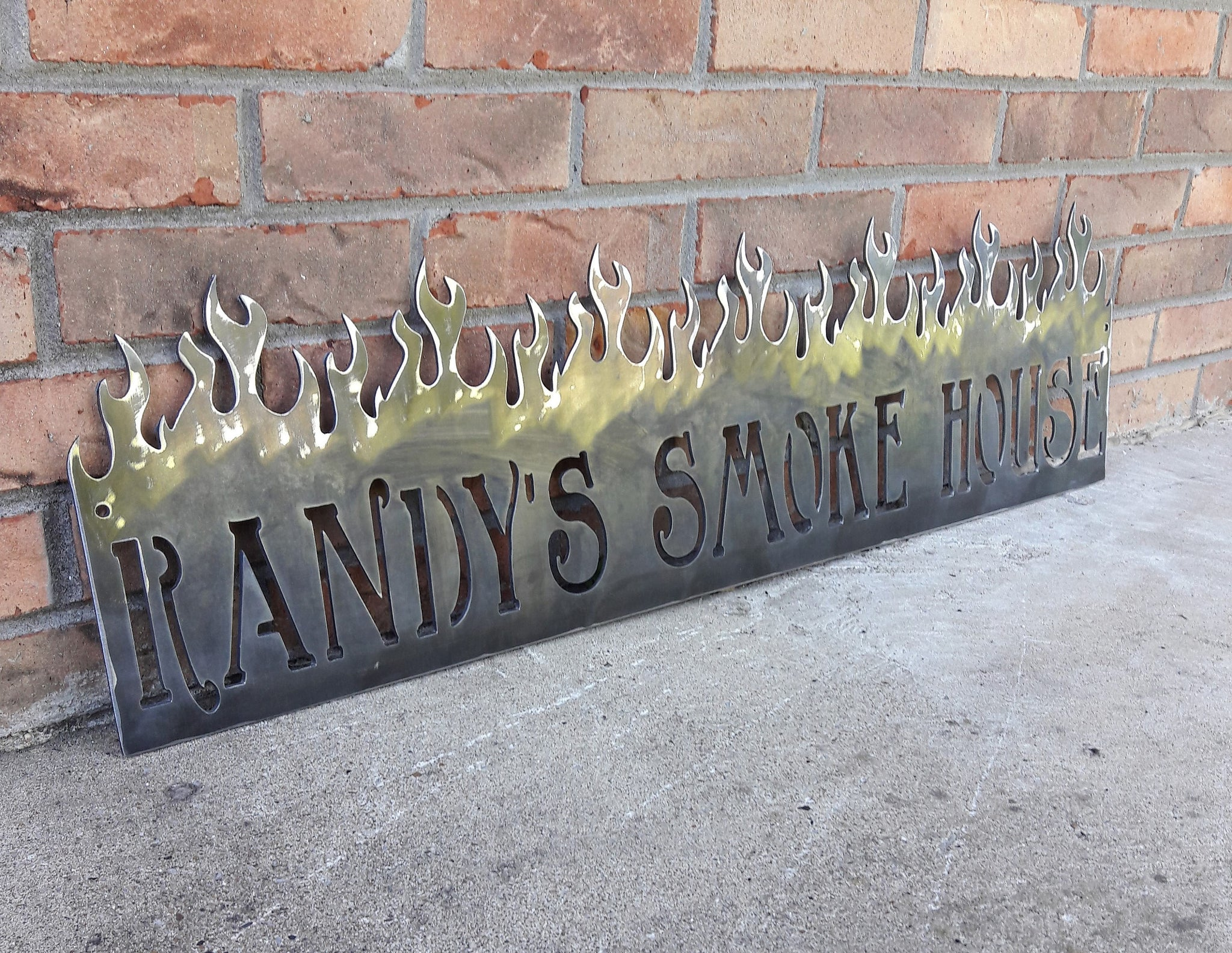 "This is a personalized metal sign that features flames at the top and reads, "" Randy's Smoke House""."