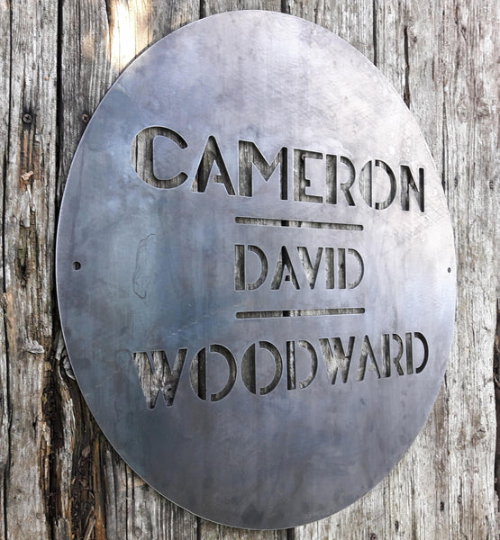 "This is a round art deco sign that has three lines of text with a straight line seperating them. The sign reads, ""Cameron David Woodward"""