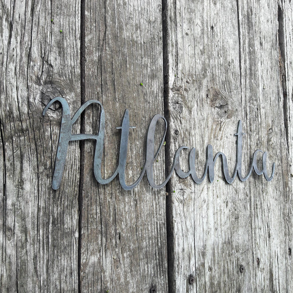 "This metal home decor is in the shape of a cursive words and reads, ""Atlanta""."