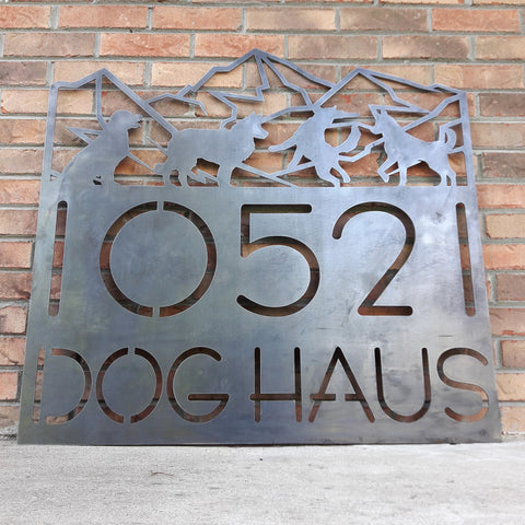 "Personalized address sign that has a mountain range with four dogs at the top. The sign is in german and reads, ""10521 DogHaus""."