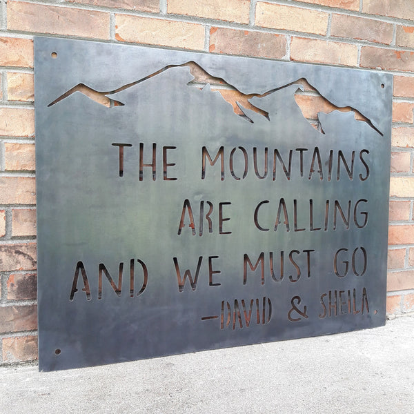 "This Metal sign has a mountain range across the top and features a quote by John Muir. The sign reads, ""The Mountains Are Calling And I must Go, David and Sheila""."