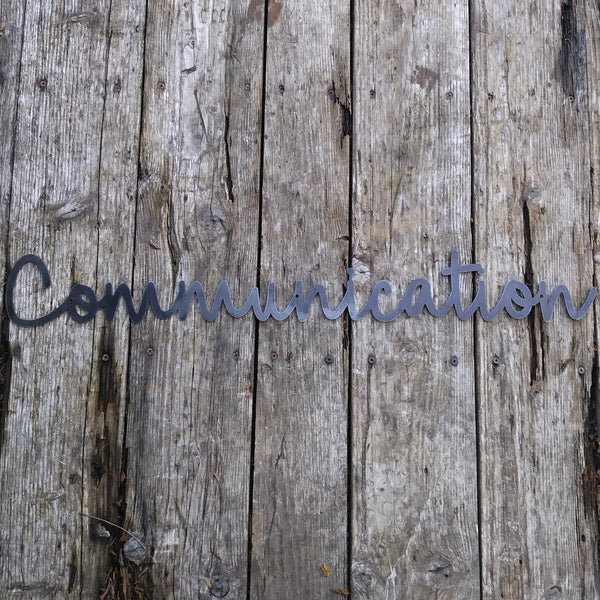 "This custom metal sign is a cursive word and reads, ""Communication"""