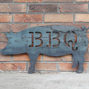 "This is a metal sign in the shape of pig with two 1/4"" mounting holes. The sig reads, ""BBQ"""