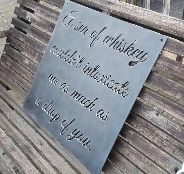 "Square plaque with cursive writing in it. The sign reads, "" A sea of whiskey couldn't intoxicate me as much as a drop of you."""