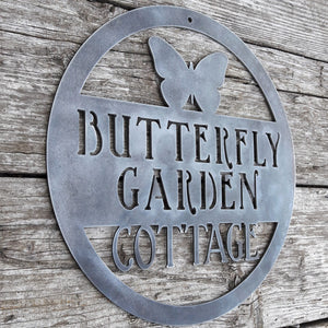 "Round metal sign with the image of a Butterfly at the top and three lines of text. The sign reads, "" Butterfly Garden Cottage""."