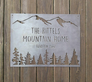 "rectangular sign with a mountain range across the top and a coniferous tree line. There are two lines of text on this sign as well as an elevation.  The sign reads, "" The Rittels Mountain Home, Elevation 8,647"""