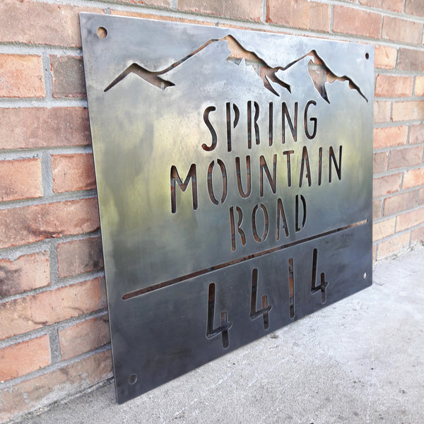 "Rectangular metal sign with half inch hanging holes. There is a mountain range at the top followed by three lines of text and then a number. The sign reads, ""Spring Mountain Road 4414"""