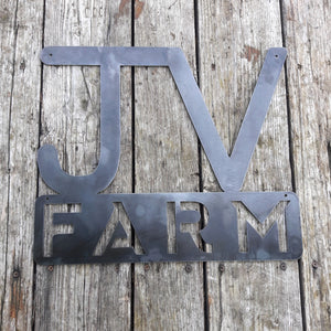 "This metal sign has two initials at the top followed by a block of text. It reads, ""JV Farm"""