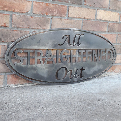 "This metal sign is an oval, it has three lines of text. The sign reads, ""All Straightened Out"""