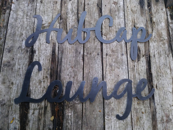 "This is a custom metal cursive sign that is powder coated black and reads' ""Hubcap Lounge""."