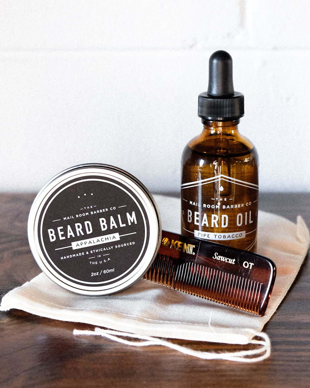 This beard kit is the perfect gift for husbands, bearded brethren, and any man that grows hair on his face. Included: Beard Balm, Beard Oil, an optional Kent FOT Comb, and a FREE Muslin Drawstring Bag. By Florence, SC sustainable brand and makers Mailroom Barber. Grooming products that are made using 100% ethically sourced ingredients and packaging.