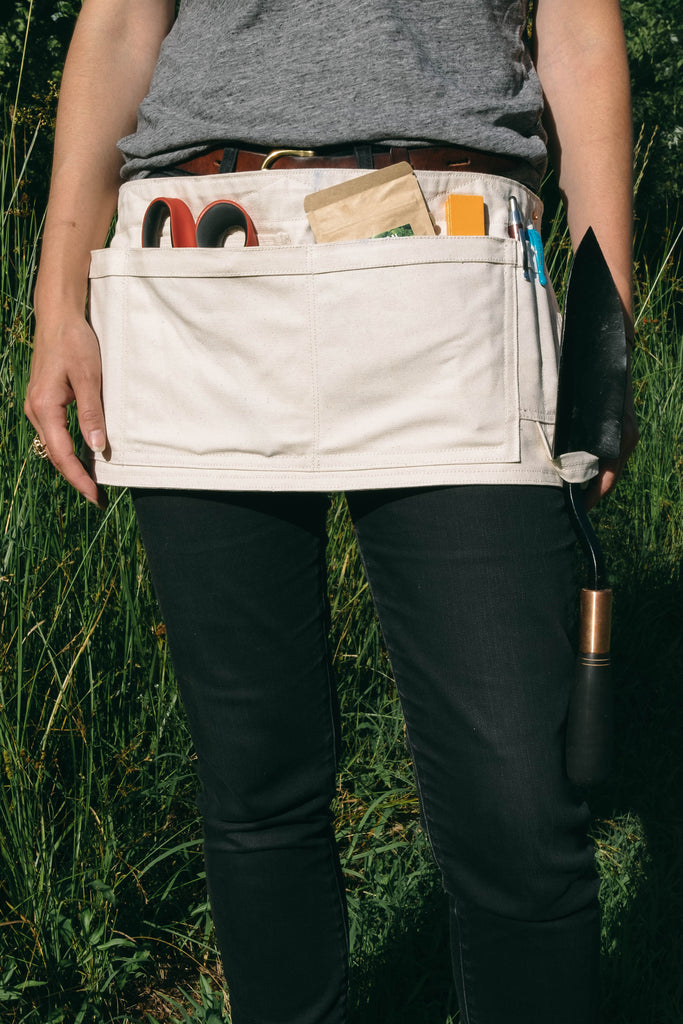The garden utility apron made is made with 100% organic cotton canvas and sustainable textiles. Durable enough to carry all your garden tools, phone, pen and hidden pockets as well as a handy tool loop. Thoughtfully designed for gardeners, fine artist, teachers and many other creatives. Made in Nashville, Tennessee.