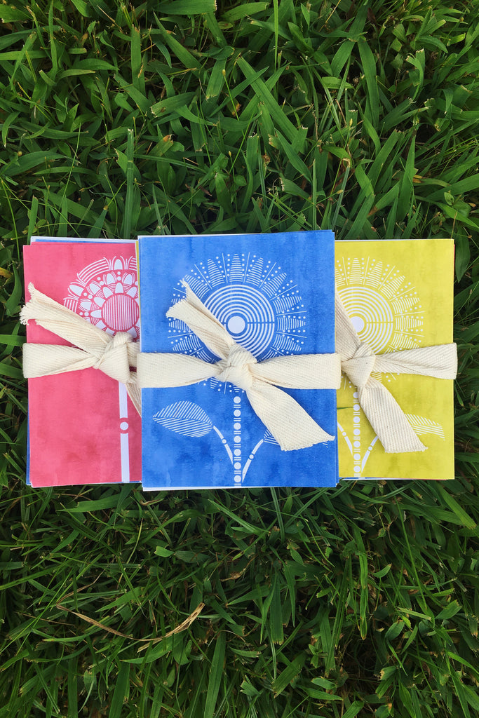 Inspired by vintage sun-faded woodblock prints, flowers are turned into minimalistic geo designs. Coral Dhalia, Indigo Sunflower, Citron Sunflower, & Indigo Poppy. Packaged in white envelopes and wrapped up in a natural cotton herringbone tape. Uses recycled paper, non-toxic inks, and wind-powered energy. Made in NYC