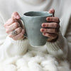 enormous indigo mug held in hands with cozy chunky cream blanket