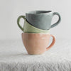 three latte mugs stacked indigo celery blush on white linen cloth
