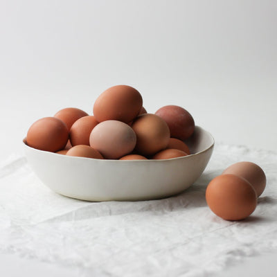 white dinner bowl with brown eggs piled inside