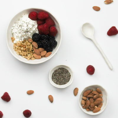 flatlay of breakfast bowl with stirring spoon almonds and chia seeds