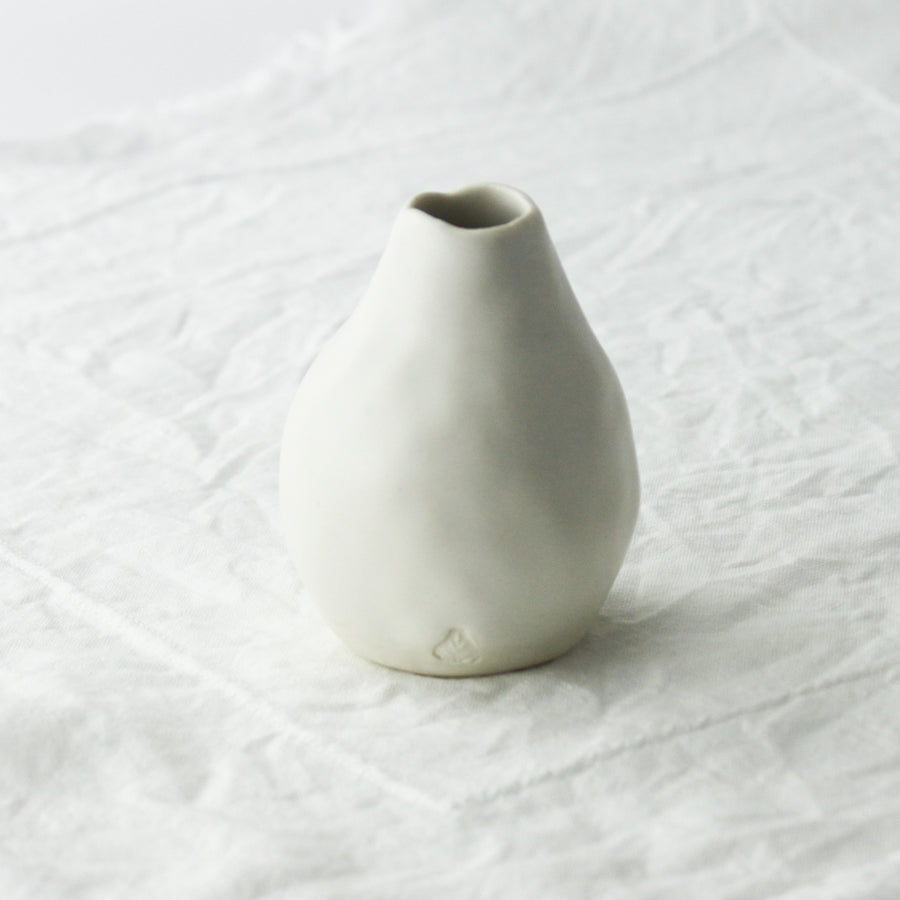 white bud vase held in hand