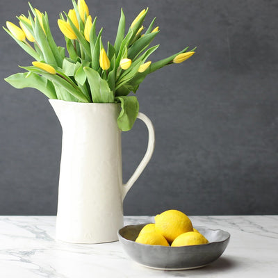 handcrafted white porcelain pitcher with yellow tulips and charcoal dinner bowl with lemons on white marble with charcoal background