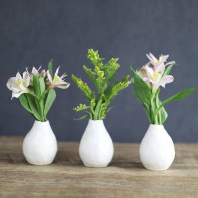 set of three bud vases with pale pink flowers lined up on wood table against dark background