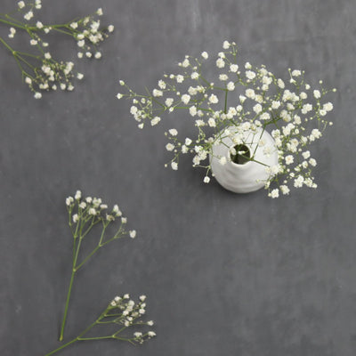 handmade white porcelain bud vase with baby's breath flat lay on charcoal background