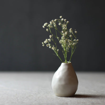 handmade white porcelain bud vase with baby's breath against dark background