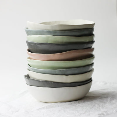 stack of dinner bowls in white charcoal cream blue green peach