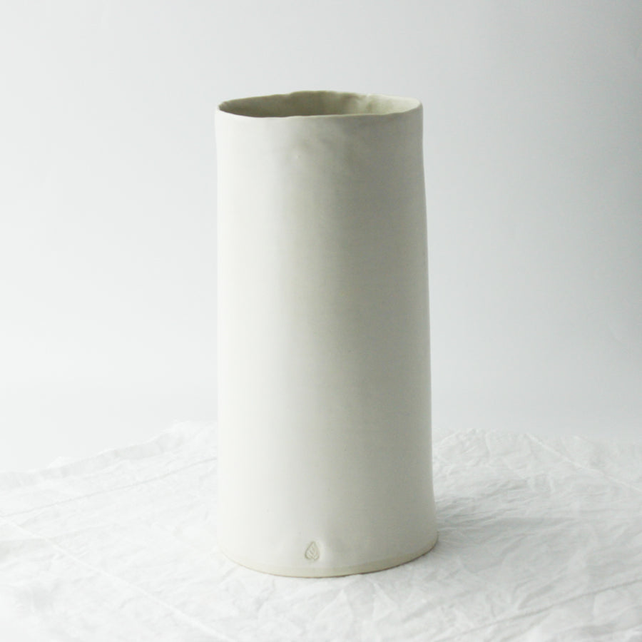 tall straight handcrafted porcelain vase with white tulips on white linen