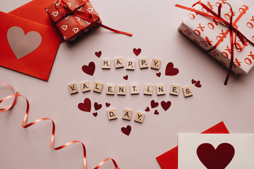 Happy Valentine's Day written in Scrabble pieces with hearts and presents.