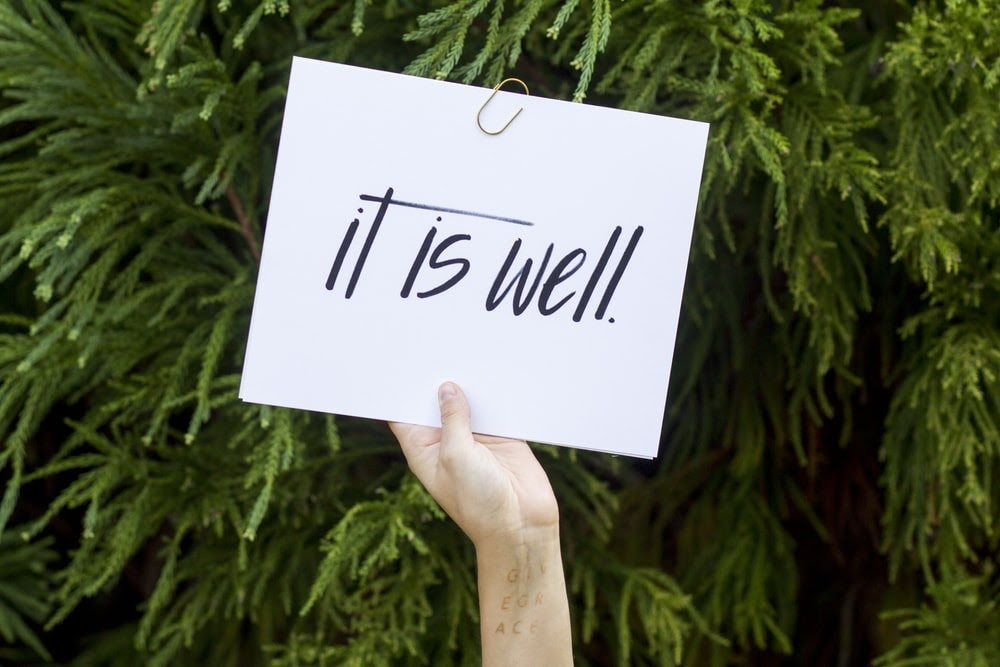 "A hand holding a sign that says ""It is well."""