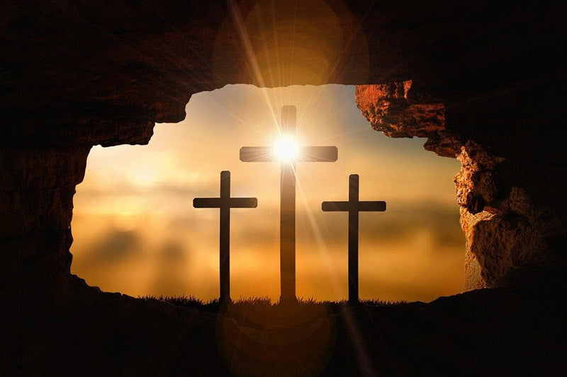 Three crosses standing outside a cave