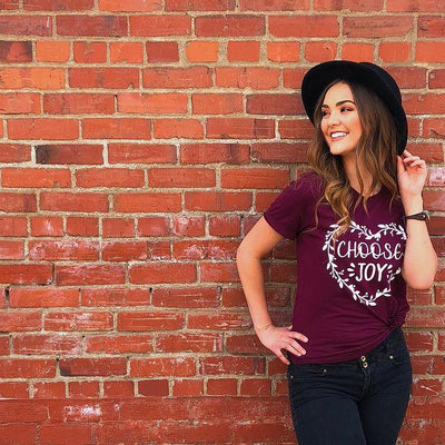 Woman smiling and leaning against a brick wall wearing choose joy Christian shirt