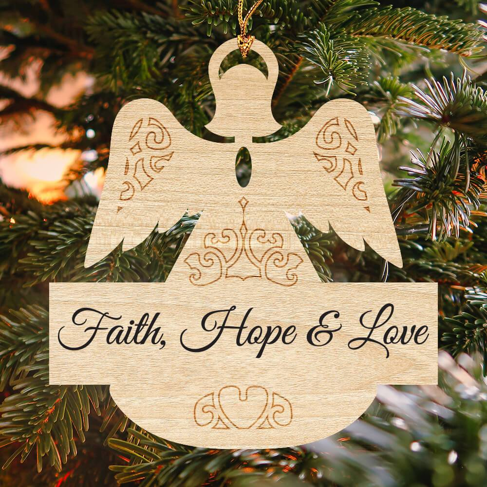 "Laser cut angel ornament that reads ""Faith, Hope & Love"" hanging from a Christmas tree"