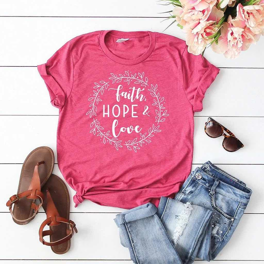 "Pink t-shirt for Valentine's Day with a floral circle that includes the text ""Faith Hope & Love"""