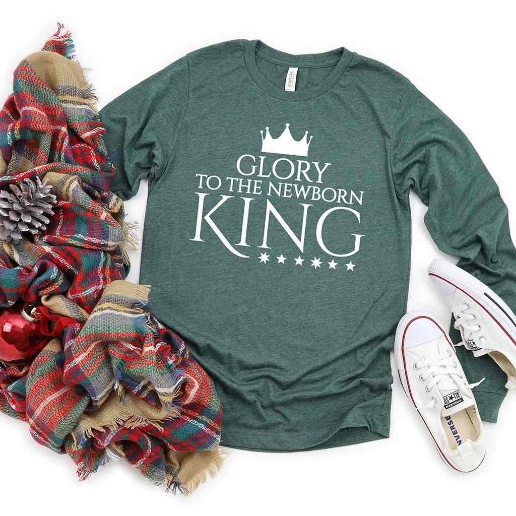"Green Christmas shirt that says ""Glory to the Newborn King"" beneath a crown"