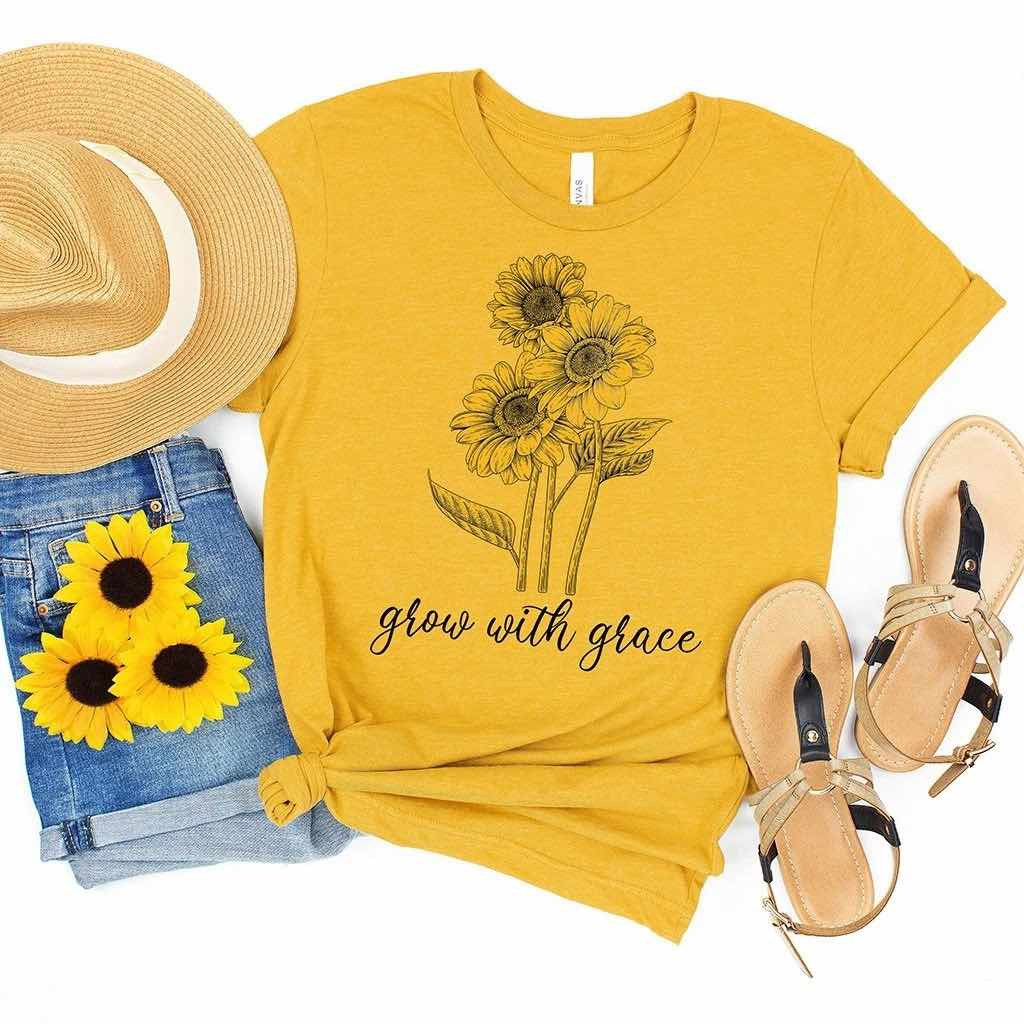 "Adorable sunflower graphic on a yellow t-shirt alongside ""grow with grace"" text"