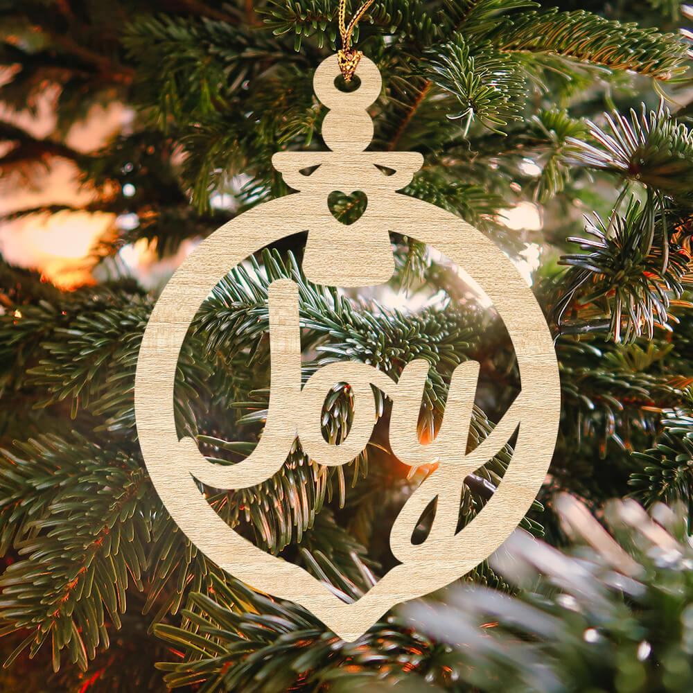 "The word ""Joy"" is laser cut from Baltic wood into this festive Christmas ornament"